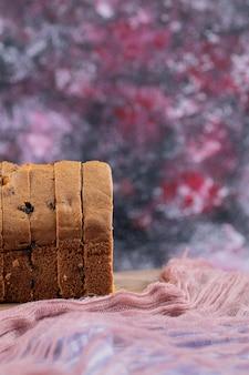 Miękkie plastry ciasta z czarną sułtanką na desce.