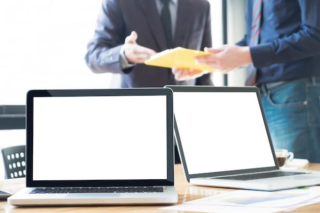 Miękkie zdjęcie na uczucie odprężenia laptopy na biurko w pakiecie office z poranek światła i rozmycie biznesowych zespołu dyskusji tła.