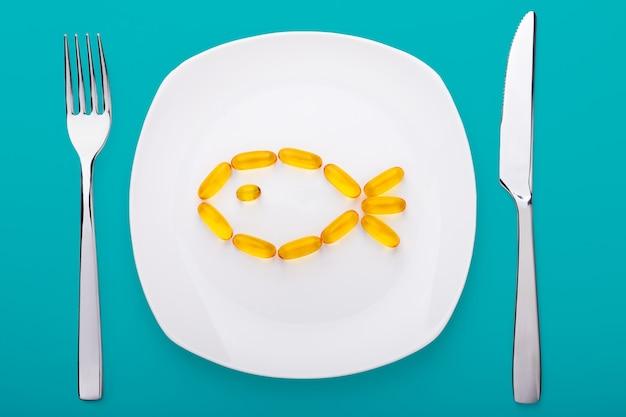 Miękkie żele oleju rybnego leżące na białej porcelanowej płytce w formie rybki