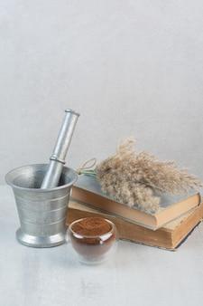 Mielona kawa, książki i moździerz i tłuczek na szarym stole. zdjęcie wysokiej jakości
