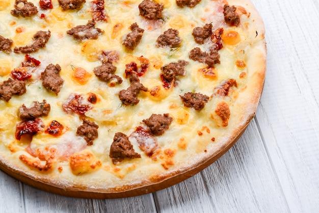Mielona mięsna pomidorowa czerwonej cebuli pizza na drewna nawierzchniowym tonowaniu