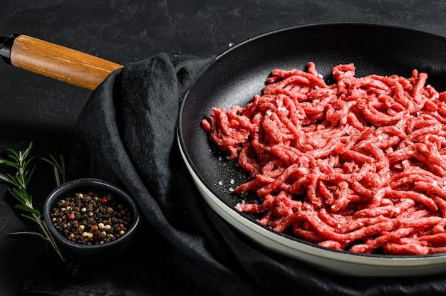 Mielona wołowina na patelni. ekologiczne mięso hodowlane. czarne tło. widok z góry