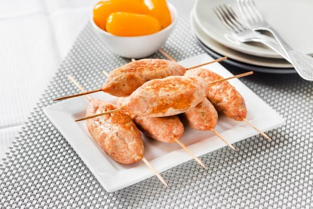 Mielone kebaby z indyka na kwadratowym talerzu i żółte pomidory marynowane w tle