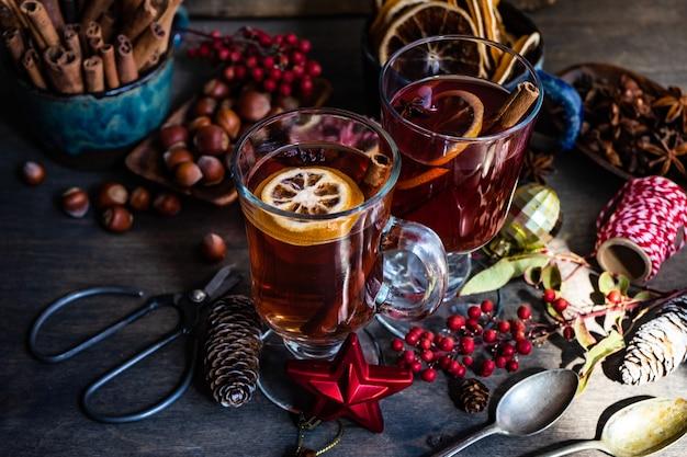 Mielone lub korzenne wino lub gluehwein z pomarańczami, gwiazdą anyżu, cynamonem i jagodami na rustykalnym drewnianym stole z miejscem na kopię