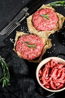 Mielone surowe mięso. pasztety mięsne gotowe do przyrządzenia. impreza grillowa. ekologiczne mięso hodowlane. czarne tło. widok z góry