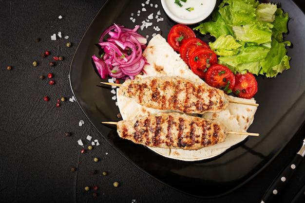 Mielony kebab z indyka z grilla (kurczak) ze świeżymi warzywami. widok z góry