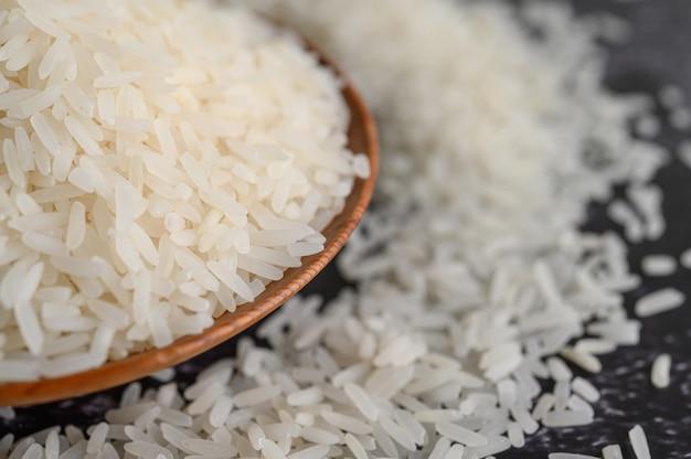 Mielony ryż w misce i drewnianą łyżką na podłodze z czarnego cementu.