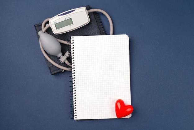 Miernik ciśnienia krwi na ciemnoniebieskim tle. papierowy notatnik z koncepcją kardiologii przestrzeni kopii. tonometr lub ciśnieniomierz.