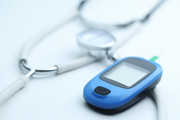 Miernik glukozy we krwi i stetoskop na białym tle