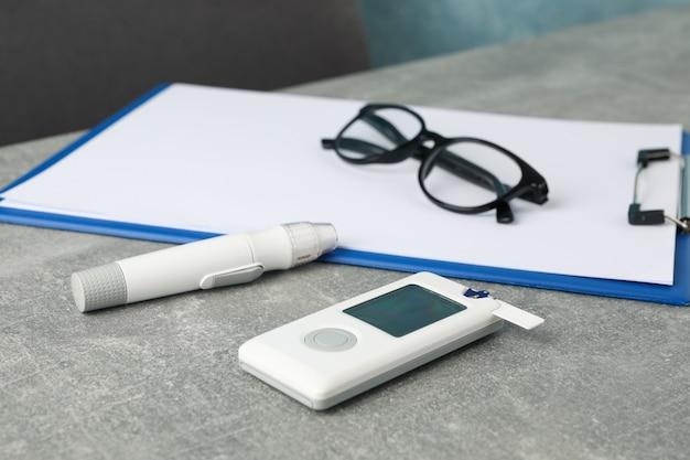 Miernik glukozy we krwi, szklanki i papierowa tabletka na szarym stole