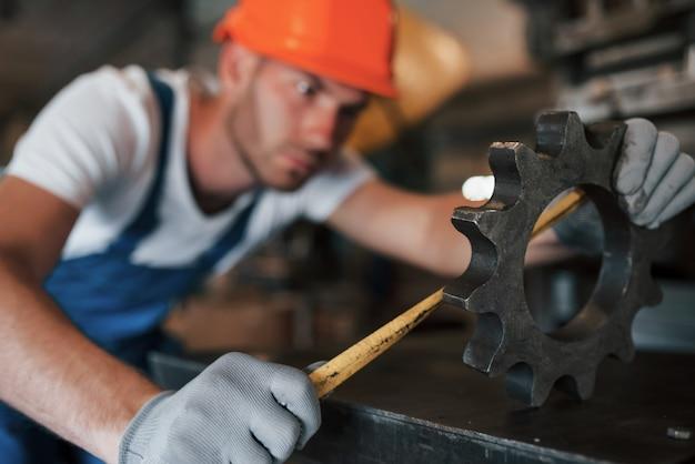 Mierzenie szczegółów. mężczyzna w mundurze pracuje nad produkcją. nowoczesna technologia przemysłowa.