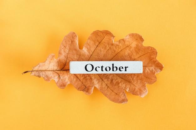 Miesiąc kalendarzowy październik na jesień liść dębu na żółto.
