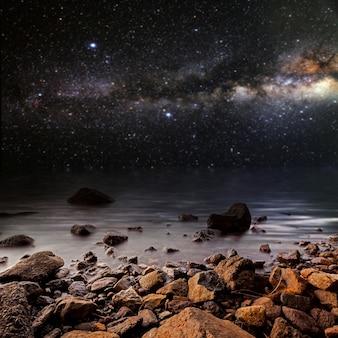 Miesiąc na powierzchni gwiaździstego nieba odbitego w morzu. elementy tego obrazu dostarczone przez nasa
