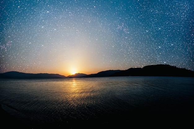 Miesiąc na powierzchni gwiaździstego nieba odbitego w morzu.