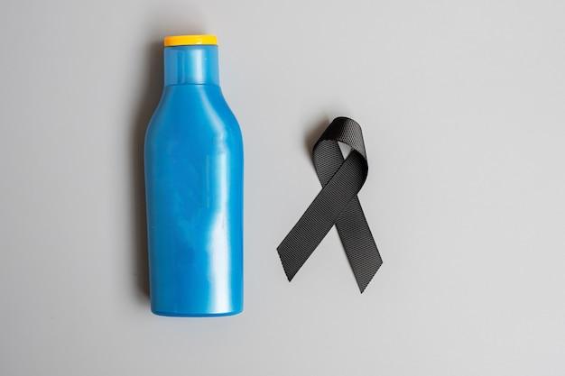 Miesiąc świadomości czerniaka i raka skóry. czarna wstążka i butelka z filtrem przeciwsłonecznym do ciała na szarym tle. koncepcja światowego dnia walki z rakiem