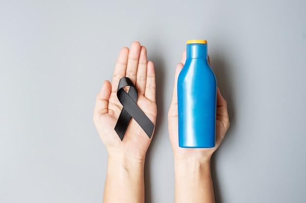 Miesiąc świadomości czerniaka i raka skóry. mężczyzna trzyma czarną wstążkę i butelkę kremu do opalania ciała na szarym tle. koncepcja światowego dnia walki z rakiem