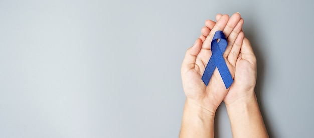 Miesiąc świadomości raka jelita grubego, mężczyzna trzymający ciemnoniebieską wstążkę za wspieranie ludzi żyjących i chorych.