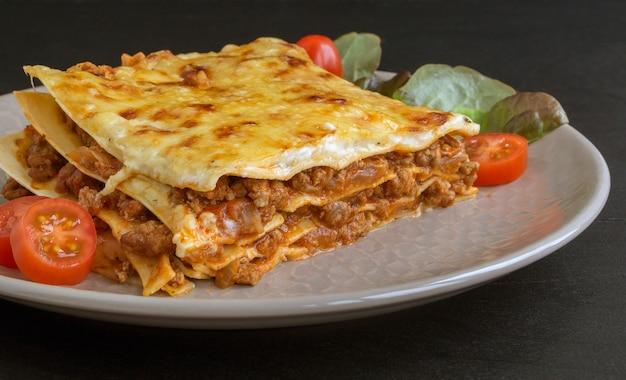 Mięsna lasagna na drewnianym stole.