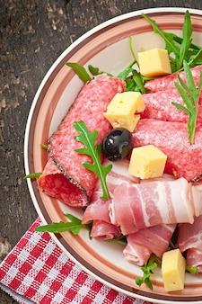 Mięsna zakąska na talerzu na starym drewnianym tle