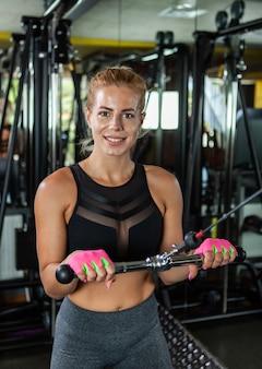 Mięśni blondynka młoda kobieta robi ćwiczenia na triceps na maszynie kablowej na siłowni.