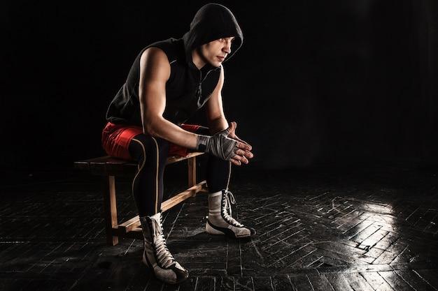 Mięśni bokser siedzi i odpoczywa na czarno