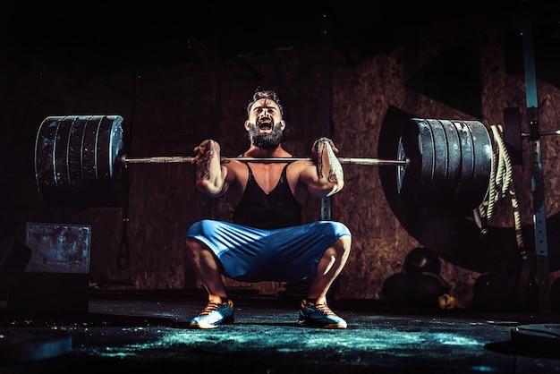 Mięśni brodaty wytatuowany mężczyzna fitness robi martwy ciąg sztangą nad głową w nowoczesnym centrum fitness.