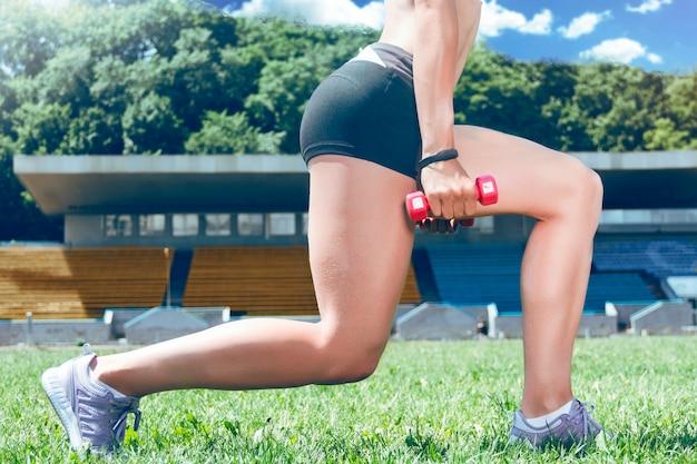 Mięśni fitness młoda kobieta sportowy robi przysiady.