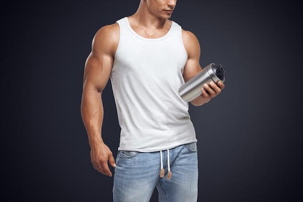 Mięśni fitness model mężczyzna trzyma butelkę shake białka