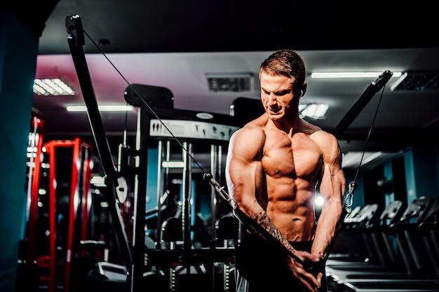 Mięśni kulturysta, poćwiczyć na siłowni, ćwiczenia na klatce piersiowej na maszynie z drutem
