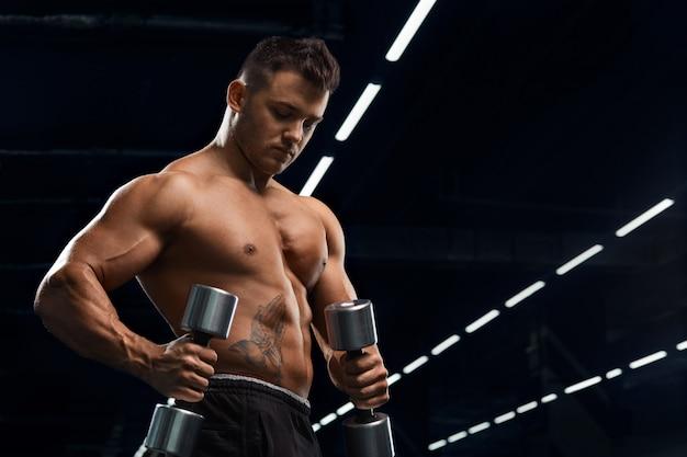 Mięśni kulturysta robi ćwiczenia z hantle w siłowni. silny, wysportowany mężczyzna pokazuje ciało, mięśnie brzucha, biceps i triceps. ćwicz, przybiera na wadze, pompuje mięśnie z hantlami.