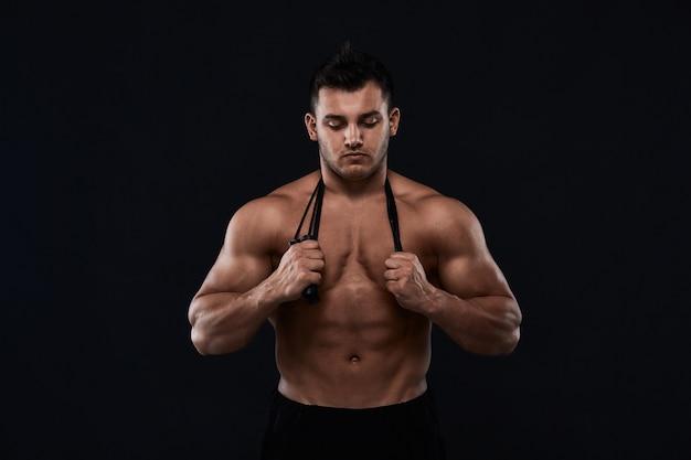 Mięśni kulturysta z skakanką na czarno. silny, wysportowany mężczyzna pokazuje ciało, mięśnie brzucha, mięśnie klatki piersiowej, biceps i triceps. ćwicz, przybiera na wadze. kulturystyka