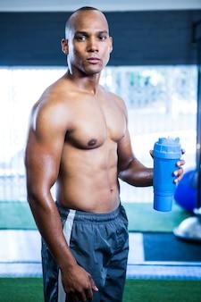Mięśni lekkoatletka lekkoatletka trzyma butelkę