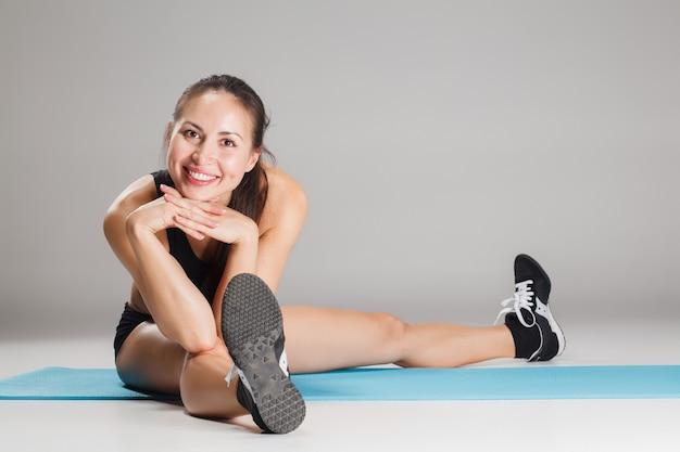 Mięśni lekkoatletka młoda kobieta, rozciągający się na szaro