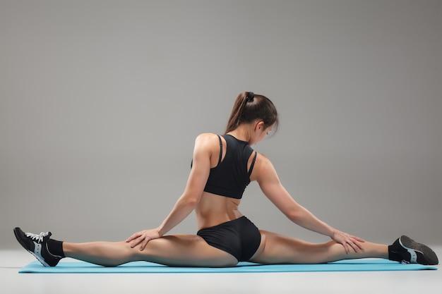 Mięśni lekkoatletka młoda kobieta siedzi w podziale na szaro