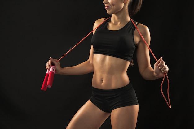 Mięśni lekkoatletka młoda kobieta z skakanka na czarno