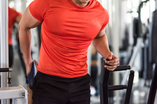 Mięśni mężczyzna rozciąga stopę i nogę w gym