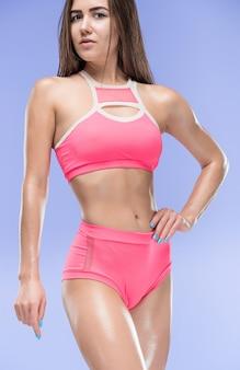 Mięśni młoda kobieta lekkoatletka pozowanie studio na niebieskim tle