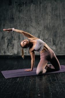 Mięśni młoda kobieta lekkoatletycznego z doskonałego pięknego ciała noszenie odzieży sportowej rozciąganie ciała i robienie ćwiczeń na macie do jogi. kobieta fitness kaukaski pozowanie studio z ciemnoszarym tle.