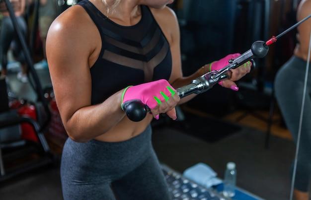 Mięśni młoda kobieta robi ćwiczenia na triceps na maszynie kablowej na siłowni.