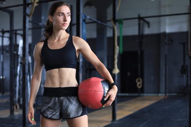 Mięśni silna kobieta niosąca piłkę lekarską na siłowni crossfit.