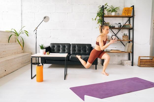 Mięśni sprawny młoda kobieta z doskonałego ciała atletyczna noszenie odzieży sportowej robi wypracowania ćwiczenia stojący boso na podłodze. pojęcie zdrowego stylu życia i aktywności fizycznej w domu.