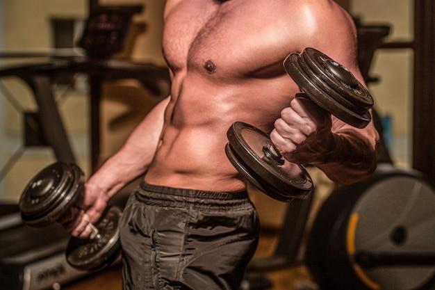 Mięśnie z hantlami. trening człowieka z hantlami. silny kulturysta, doskonałe mięśnie naramienne, barki, bicepsy, triceps i klatkę piersiową. hantle. umięśnieni kulturyści, ćwiczenia z hantlami.