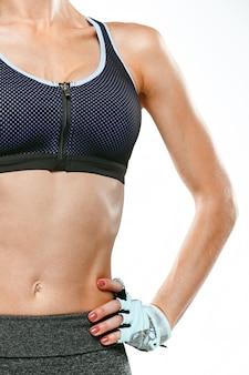 Mięśniowa młodej kobiety atleta na bielu