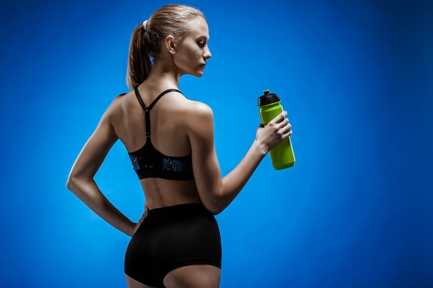 Mięśniowa młodej kobiety atleta z wodą na błękicie