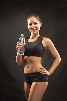 Mięśniowa młodej kobiety atleta z wodą na czerni