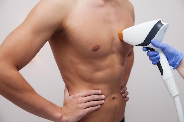 Mięśniowy atleta mężczyzna z gładką jasną skórą. depilacja i depilacja włosów w salonie kosmetycznym. koncepcja depilacji laserowej męskiej. kosmetyczka za pomocą nowoczesnego aparatu do zabiegów. pielęgnacja skóry i urody