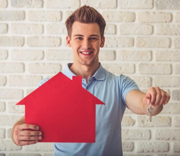 Mięśniowy facet w błękitnej koszulce trzyma papierowego dom.