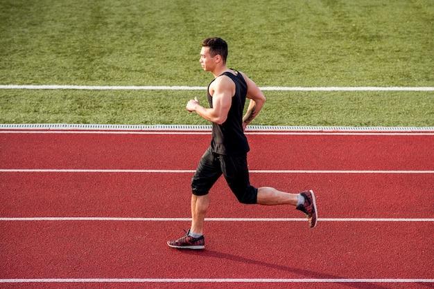 Mięśniowy męski biegacz biega na czerwonym biegowym śladzie