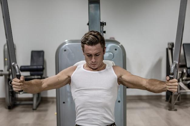 Mięśniowy mężczyzna ćwiczy na nowożytnej maszynie