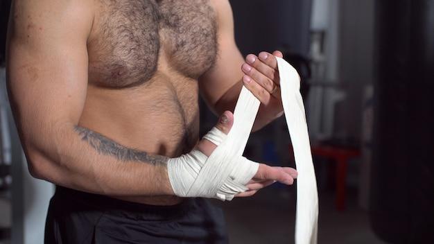 Mięśniowy mężczyzna kładzenie na uderzać pięścią opakunki w sprawności fizycznej studiu.